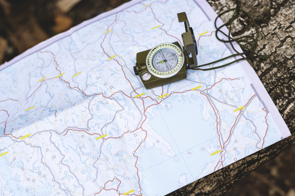 Map and compass on tree trunk